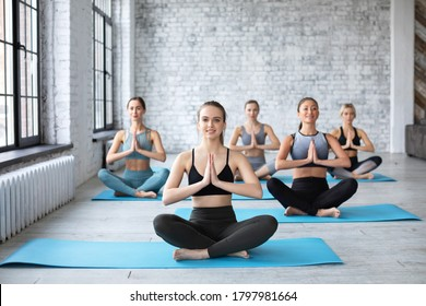 Smiling women and their teacher practicing yoga in gym. Concept of relaxation and meditation.