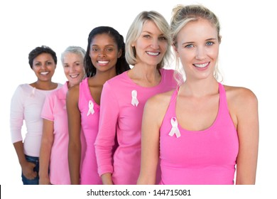 Smiling women wearing pink and ribbons for breast cancer on white background