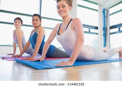 Smiling women at yoga class in fitness studio