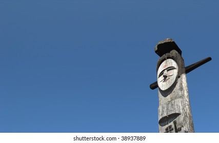Smiling wooden idol on the background of blue sky.