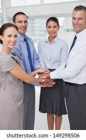 Smiling work team joining hands together in bright office
