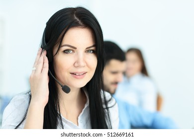 Smiling worker doing her job with a headset while looking at the camera in the call center