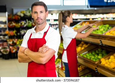 Smiling worker in front of colleague in grocery store