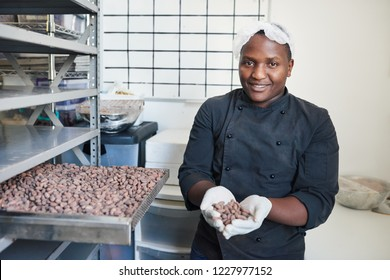 Smiling worker holding a pile of cocoa beans while standing in an artisanal chocolate making factory