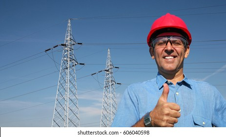 Smiling Worker Near Electrical Transmission Towers. Thumb up given by smiling engineer. A line of electrical transmission towers carrying high voltage. Portrait of an electrical engineer.