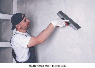 Smiling worker in overalls, cap and gloves plastering a wall with finishing putty using a putty knife. Repair work and construction concept. Toned