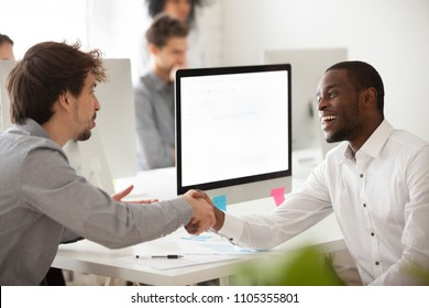 Smiling worker shaking hand of Caucasian client, greeting, making good first impression, black employer congratulating job applicant with successful interview, handshaking. Mock up computer  screen
