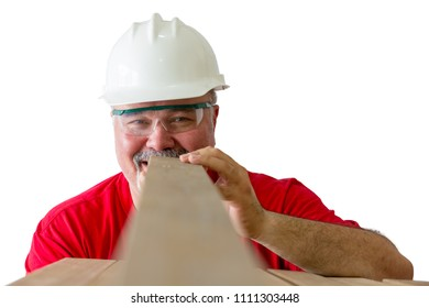 Smiling worker wearing helmet with protective glasses inspecting quality of wooden plank isolated against white background