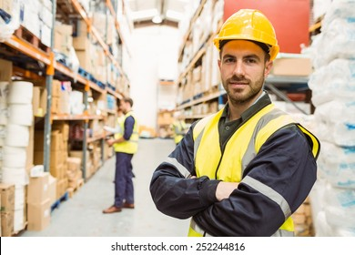 Smiling worker wearing yellow vest with arms crossed in a large warehouse
