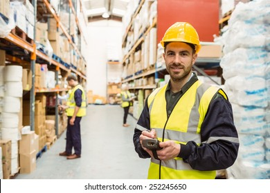 Smiling worker wearing yellow vest using handheld in a large warehouse