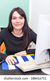 Smiling working woman behind computer monitor and keyboard