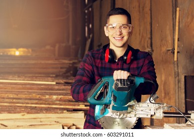 Smiling workman dressed in the checkered shirt working with circular saw at the sawmill. Timbers on background.