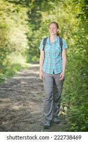 Smiling young active woman walks on a forest path on a sunny summer day.