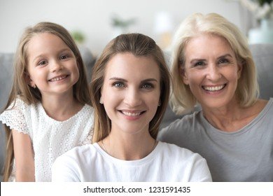 Smiling young adult woman looking at camera with old mother and little kid daughter, millennial mom posing with child girl and grandmother, happy three generation family together, headshot portrait