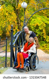 smiling young adult woman on wheelchair and older man in the park