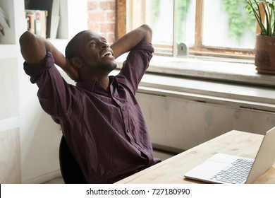 Smiling young african american businessman relaxing, stretching his back at workplace in modern office. Taking a break from heavy workflow, chilling after positive meeting, finished project concept.