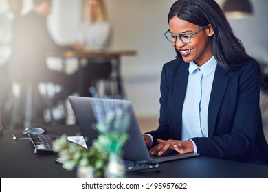 Smiling young African American businesswoman working on a laptop at her desk in a bright modern office with colleagues in the background - Shutterstock ID 1495957622