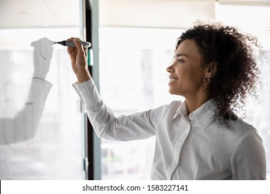 Smiling young african American businesswoman busy writing on white board developing company financial business plan, millennial biracial woman brainstorm involved in creative thinking use flip chart