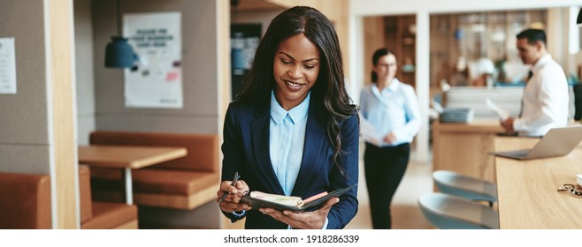 Smiling young African American businesswoman writing notes in her day planner while walking through a diverse modern office