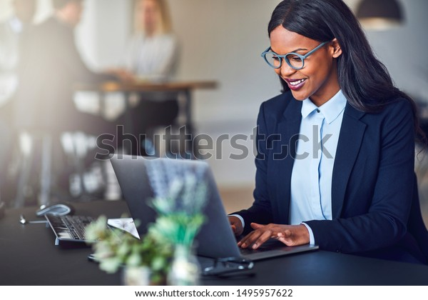 Smiling young African American businesswoman working on a laptop at her desk in a bright modern office with colleagues in the background