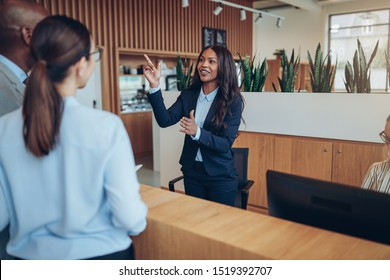 Smiling young African American concierge giving two guests directions to their room while checking them into her hotel