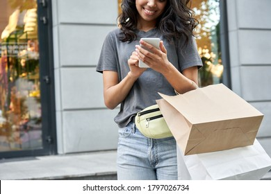 Smiling young African American ethnic girl shopper customer standing on city street holding shopping bags and smart cell phone using mobile fashion sale ecommerce app near shop mall store, closeup.