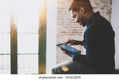 Smiling young African American freelancer touching screen digital tablet while working in new project at home.Black businessman looking for information on Internet.Blurred,color filter,flares