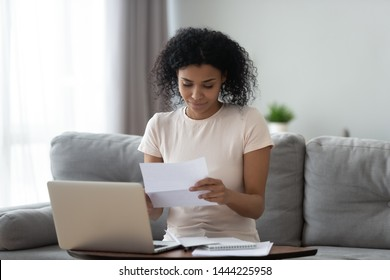 Smiling young african american girl student reading paper post mail letter of advice bank statement invoice sit on sofa, happy black woman holding bill document notification doing paperwork at home