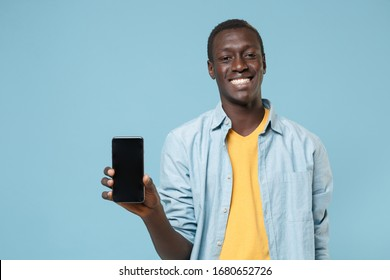 Smiling young african american man guy in casual shirt, yellow t-shirt posing isolated on blue wall background. People lifestyle concept. Mock up copy space. Hold mobile phone with blank empty screen - Shutterstock ID 1680652726