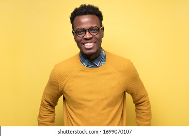 Smiling young african american man with glasses smiling confident against yellow background