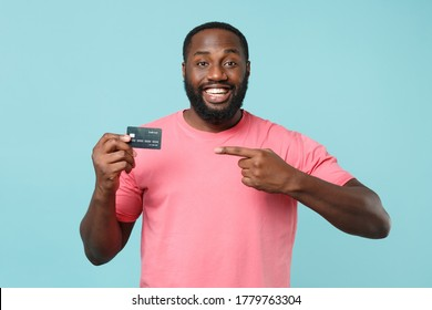 Smiling young african american man guy in casual pink t-shirt isolated on blue wall background studio portrait. People lifestyle concept. Mock up copy space. Pointing index finger on credit bank card