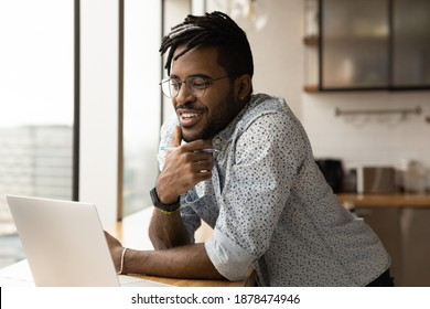 Smiling young African American man look at computer screen watch webinar on gadget make notes. Happy millennial biracial male work online or study distant on laptop in home office. Technology concept. - Shutterstock ID 1878474946
