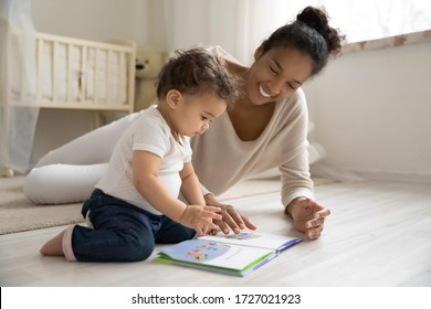 Smiling young african American mother sit on warm floor play with little infant toddler child, happy biracial mom relax have fun read book with small baby girl at home, motherhood, childcare concept - Shutterstock ID 1727021923