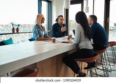 Smiling young African American office worker talking with colleagues during a meeting around a boardroom table