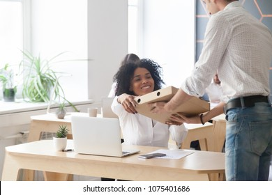 Smiling young african american woman employee taking pizza box from courier sitting at work desk, black office worker ordered meal food delivery service on corporate lunch break sitting at workplace