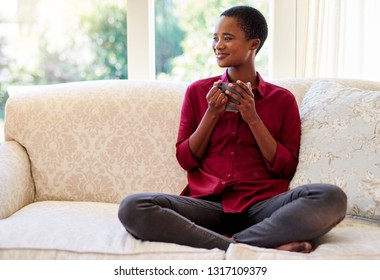 Smiling young African American woman sitting with her legs crossed on her sofa at home drinking a cup of coffee