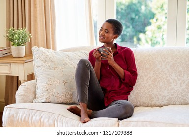Smiling young African American woman drinking a cup of coffee while relaxing on her living room sofa at home