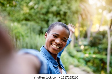 Smiling young African American woman taking selfies while enjoying a day out in a park in the summer