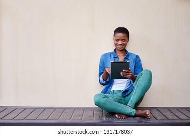Smiling young African American woman sitting on her patio floor outside using a digital tablet