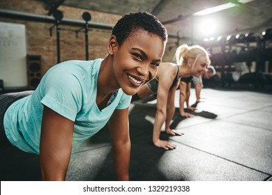 Smiling young African American woman in sportswear doing pushups on a gym floor during a workout class in a gym