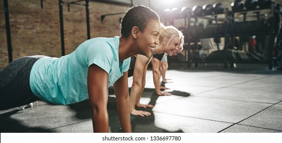 Smiling young African American woman in sportswear doing pushups at the gym with a group of friends during an exercise class