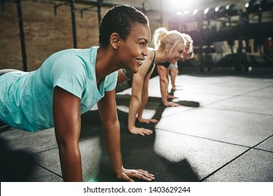 Smiling young African American woman in sportswear doing pushups during a workout class on the floor of a gym