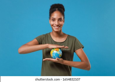 Smiling young african american woman girl in casual t-shirt posing isolated on bright blue background studio portrait. People emotions lifestyle concept. Mock up copy space. Hold Earth world globe