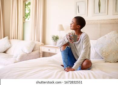 Lächelnde junge Afroamerikanerin, die auf ihrem Bett sitzend und eine Tasse Kaffee trinkt und über den bevorstehenden Tag nachdenkt