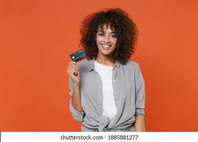 Smiling young african american woman 20s in gray casual clothes isolated on orange background studio portrait. People sincere emotions lifestyle concept. Mock up copy space. Hold credit bank card