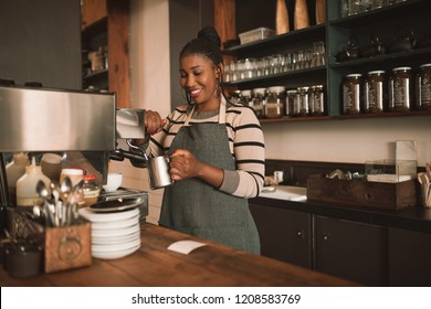Smiling young African barista frothing milk for a cappuccino behind the counter of her trendy cafe