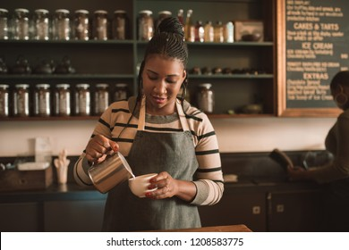 Smiling young African barista pouring frothed milk into a cup of cappuccino behind the counter of her trendy cafe