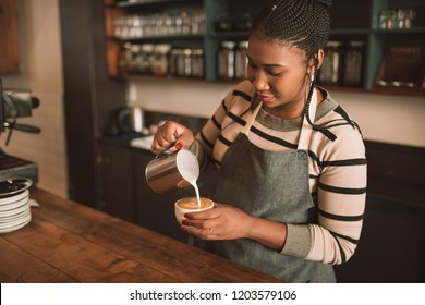 Smiling young African barista standing behind the counter of her trendy cafe pouring frothed milk into a cup of cappuccino