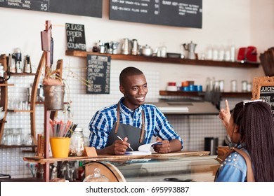Smiling young African barista talking to a customer and writing down an order in a notebook while standing at the counter of a cafe