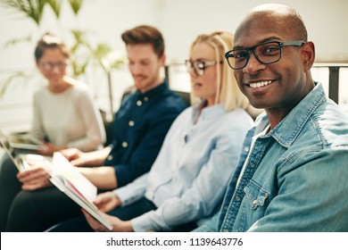 Smiling young African businessman sitting on a sofa with a diverse group of colleagues in a modern office